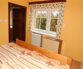 Ložnice A s manželskou postelí a nočním stolkem