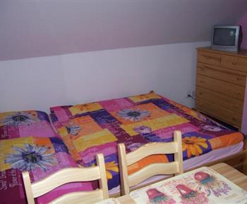 Růžový apartmán s lůžky, komodou, televizí, stolem a židlemi