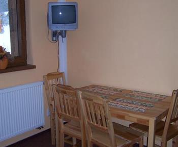 Oranžový apartmán se stolem, židlemi a televizí