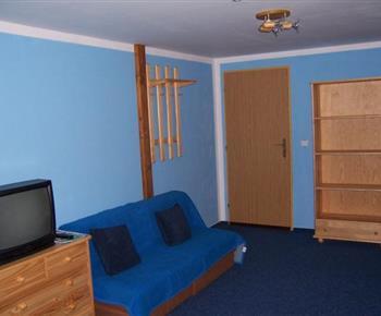 Modrý apartmán s pohovkou, televizí, komodou a odkládací stěnou