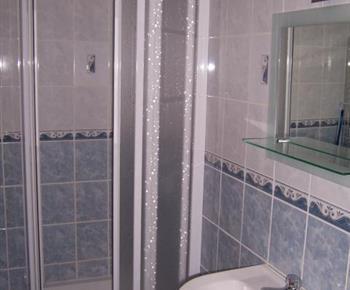 Modrý apartmán se sprchovým koutem, umývadlem a toaletou