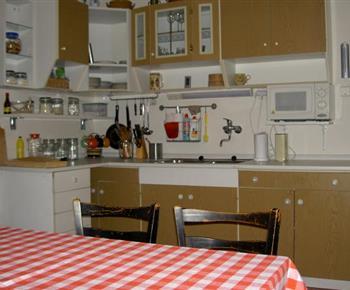 Kuchyně s elektrickým sporákem, lednicí, varnou konvicí, stolem a židlemi