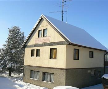 Zimní pohled na chatu pod sněhovou pokrývkou