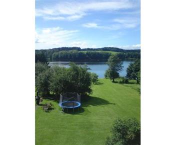Výhled z pokoje na zatravněnou zahradu a jezero