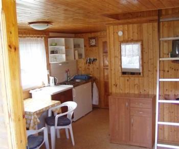 Pohled ze společenské místnosti do kuchyňky s lednicí, vařičem a rychlovarnou konvicí