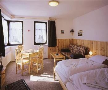 Ložnice s lůžky, skříní, pohovkou, stolem, židlemi a televizí