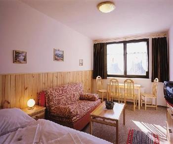 Ložnice s lůžky, skříňkou, pohovkou, stolem, židlemi a televizí