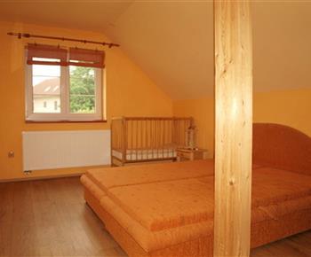 Ložnice s manželským dvoulůžkem a dětskou postýlkou