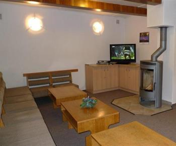 Společenská místnost s pohovkou, stolky, skříňkou, televizí a kamny