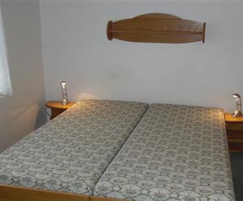 Pokoj s lůžky, nočním stolkem, poličkou a lampičkou