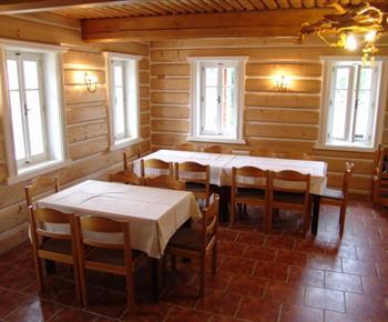 Společenská místnost se stoly a židlemi je součást kuchyně