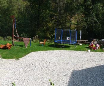 Prolézačky a trampolína na oplocené zahradě u chalupy