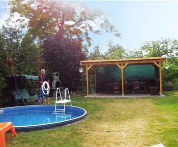 Bazén a posezení na zatravněném pozemku
