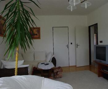 Celkový pohled na obývací pokoj se sedací soupravou a televizorem