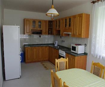 Pohled na kuchyňskou linu s lednicí, rychlovarnou konvicí a jídelním stolem