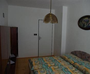Pohled na pokoj s manželským lůžkem a obývací stěnou