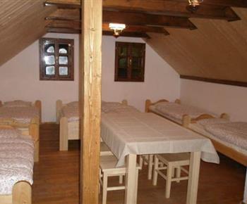 Pokoj s lůžky, stolem a židlemi