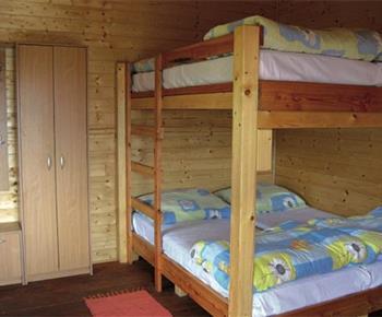 Pokoj v chatce s lůžky, skříňkou, stolkem a židlemi