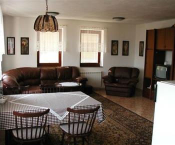 Obývací pokoj se sedací soupravou, televizí a jídelním koutem
