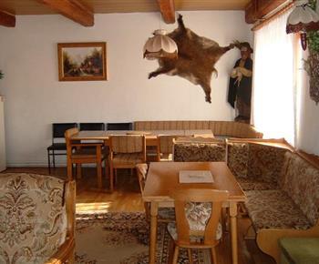 Společenská místnost 2.část s jídelními stoly a sedací soupravou