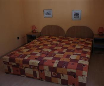 Pokoj C s manželskou postelí, nočními stolky a lampičkami