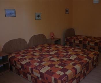 Pokoj D s lůžky, nočními stolky a lampičkami