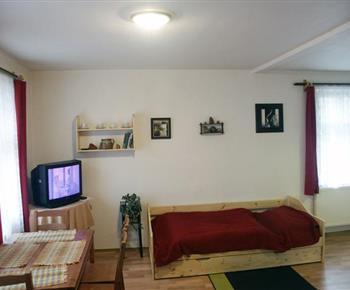 Ložnice s lůžky, stolem, židlemi a televizí