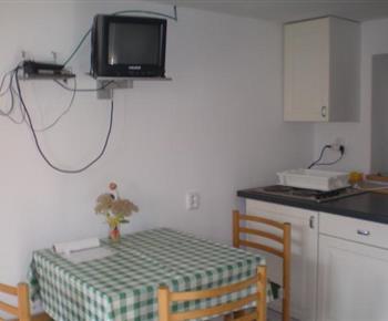 Kuchyňka v suterénu s jídelním koutem, televizí a satelitním příjmem