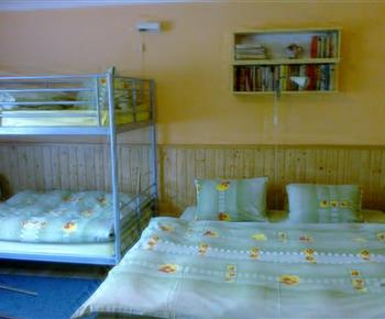 Pokoj D s lůžky, nočními stolky a lampičkami a dětskou postýlkou