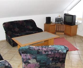Obývací pokoj s televizí, sedačkou a hifi věží