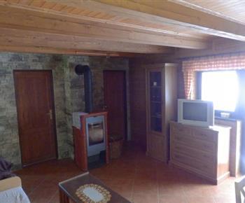Společenská místnost v apartmánu A s televizí a krbovými kamny