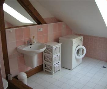 Pohled na sociální zařízení s umyvadlem, zrcadlem a pračkou