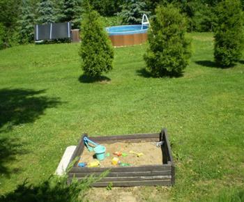 Pohled na zahradu s dětským pískovištěm a bazénem
