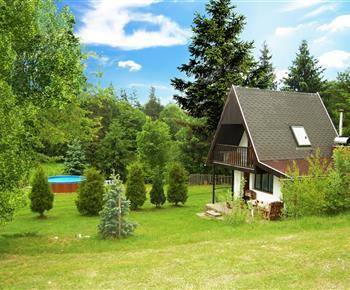 Celkový pohled na objekt s přilehlým lesem a nadzemním bazénem