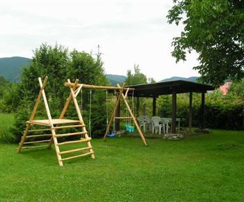 Udržovaná zahrada s houpačkou a zastřešeným psezením
