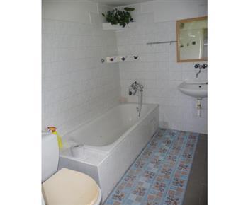 Pohled na sociální zařízení s vanou, umyvadlem a  zrcadlem