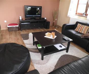 Obývací pokoj se sedací soupravou, konferenčním tolem a televizorem