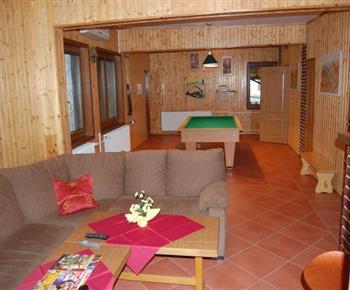 Obývací místnost se sedačkou, televizí a kulečníkem