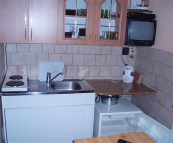 Společná vybavená kuchyňka v přízemí s televizí a posezením