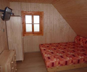 Pohled na pokoj s manželským lůžkem, televizí a šatní skříní