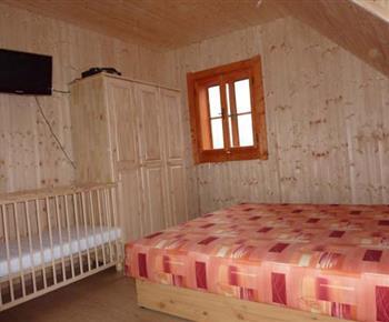 Pohled na pokoj s manželským lůžkem, dětskou postýlkou a vybavením