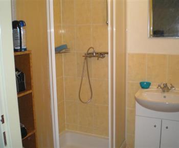 Koupelna se sprchovým koutem, umyvadlem a zrcadlem