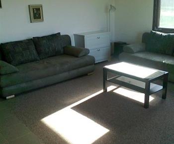 Pohled na obytný obývací pokoj se sedací soupravou a konferenčním stolem