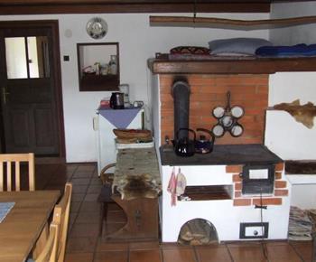 Obytná kuchyně s pecí, lůžky a jídelním stolem