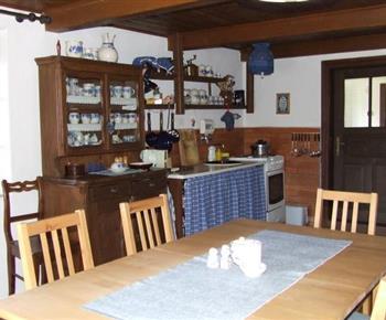 Obytná kuchyně s konvicí, lednicí a jídelním stolem
