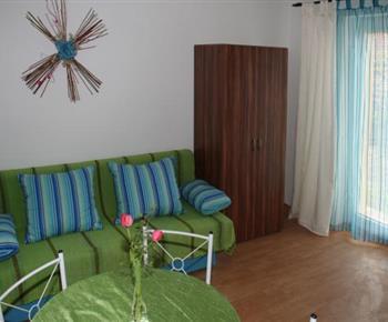 Čtyřlůžkový apartmán - obytná místnost s kuchyňskou linkou, pohovkou a televizí