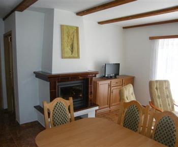 Obytná místnost s krbem, televizí a jídelním koutem