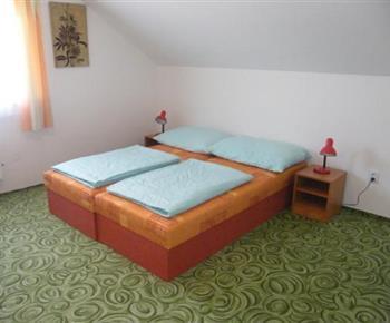 Ložnice s lůžky, nočními stolky a lampičkami v patře