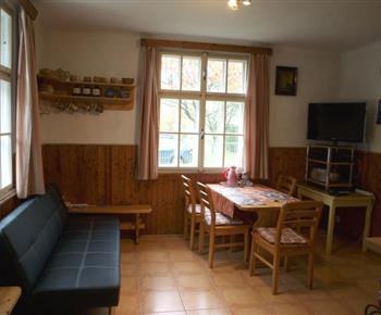 Společenská místnost s televizí, krbovými kamny a jídelním koutem
