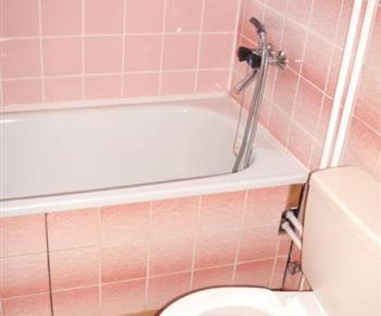 Koupelna s vanou, toaletou a umyvadlem v apartmánu B